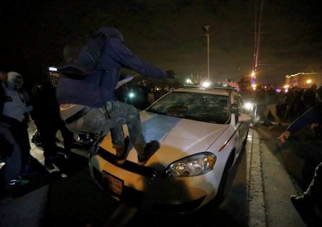 Protesters vandalize a police car outside the Ferguson Police Department in Ferguson, Missouri, after a grand jury returned no indictment in the shooting of Michael Brown