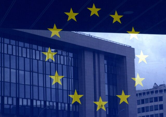 European Council building is reflected in a photograph of the EU flag on the wall of the European Council building, in Brussels