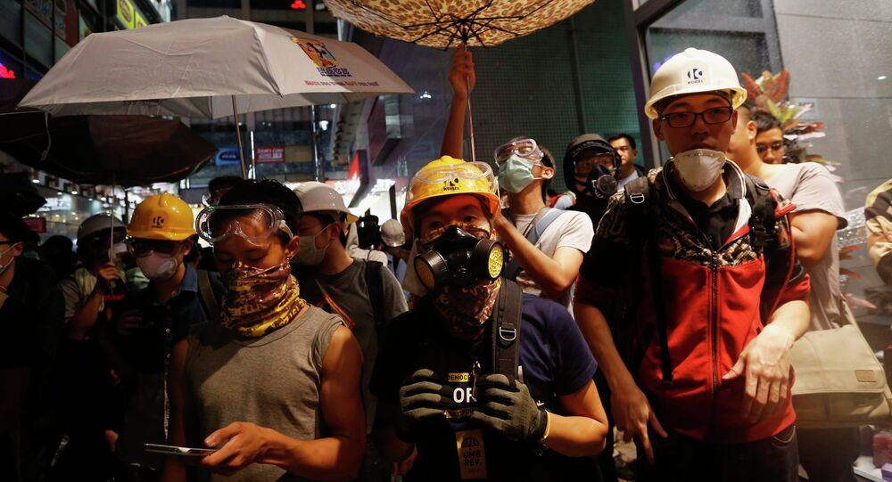 Protesters protect themselves from being sprayed with tear spray during a confrontation with riot police at Mongkok shopping district in Hong Kong