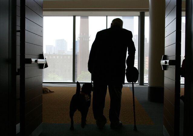 Wilson Hulley of Chevy Chase, Md., and his service dog Laurel leave at the end of the New England Assistance Dog Services (NEADS) graduation for dogs who assist the deaf and disabled at the Boston Convention and Exhibition Center