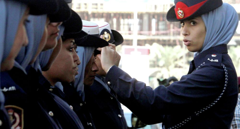 A Bahraini policewoman adjusts a colleague's hat outside the Manama, Bahrain