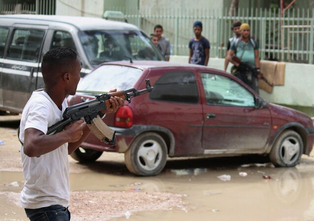 A man with an armed group of Libyan people holds a weapon to defend their local area from Islamic militias in Benghazi, Libya, Thursday, Oct. 23, 2014