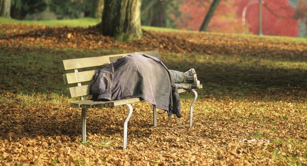 Homeless man sleeping on park bench in Stanley Park, Vancouver, British Columbia, Canada