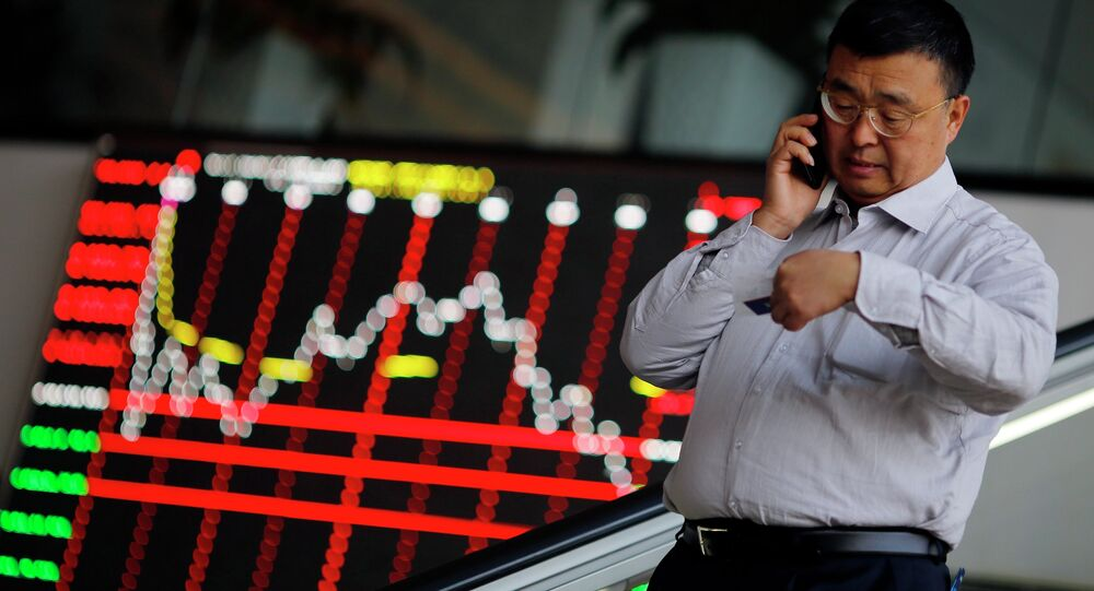 A man talks on the phone inside the Shanghai Stock Exchange building at the Pudong financial district in Shanghai November 17, 2014