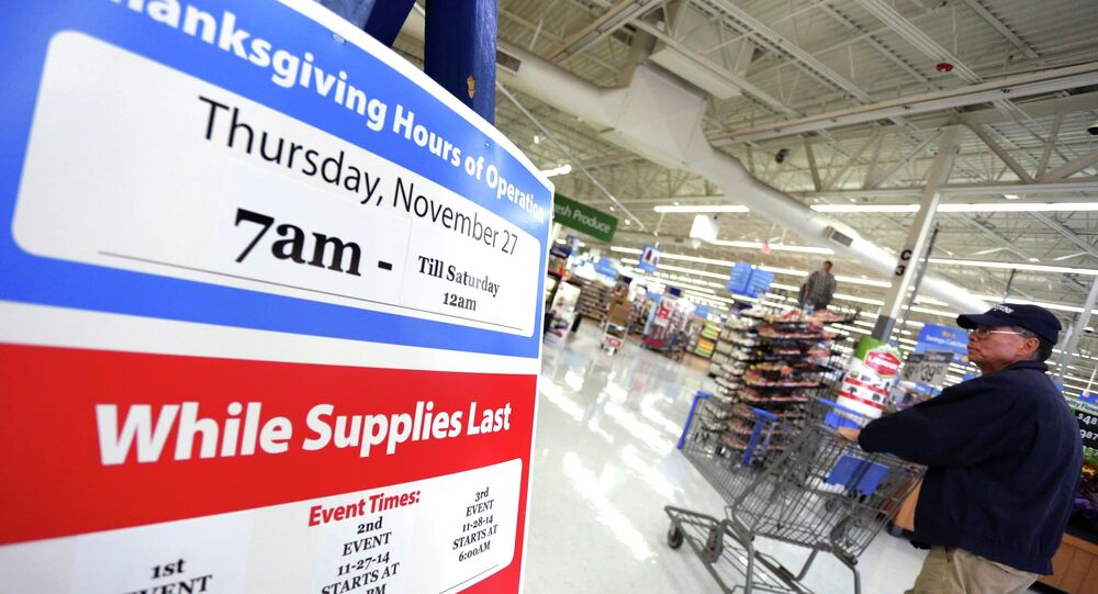 A man walks near a sign at Walmart as the store prepares for Black Friday in Los Angeles, California November 24, 2014
