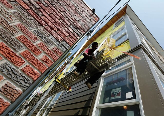 In this Friday, Aug. 17, 2012, file photo, a worker adjusts a scaffold at the site of a new residential construction project in the East Boston neighborhood of Boston