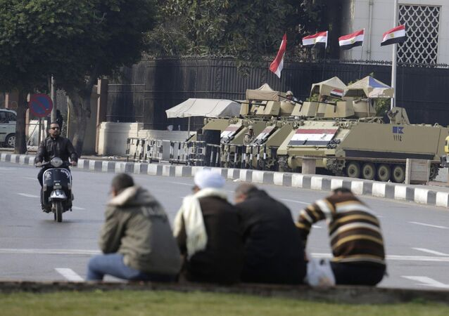 Armored vehicles stand alert at the entrance of Tahrir Square in Cairo, Egypt, Friday, Nov. 28, 2014