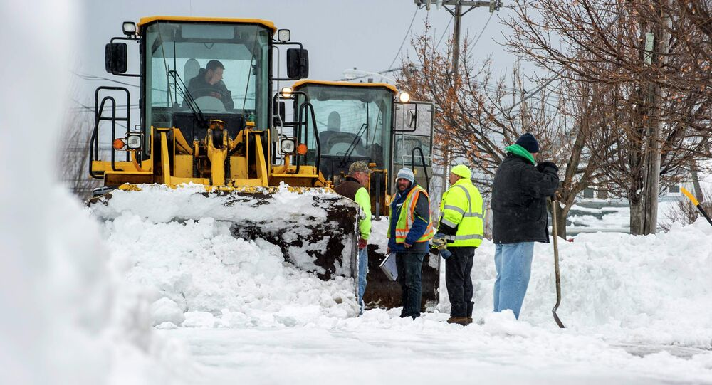 People, with help from heavy equipment, remove snow in South Buffalo, New York November 22, 2014