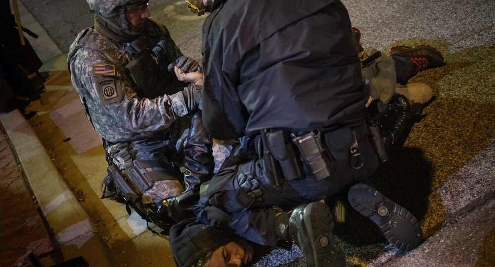 A policeman and member of the National Guard detain a man