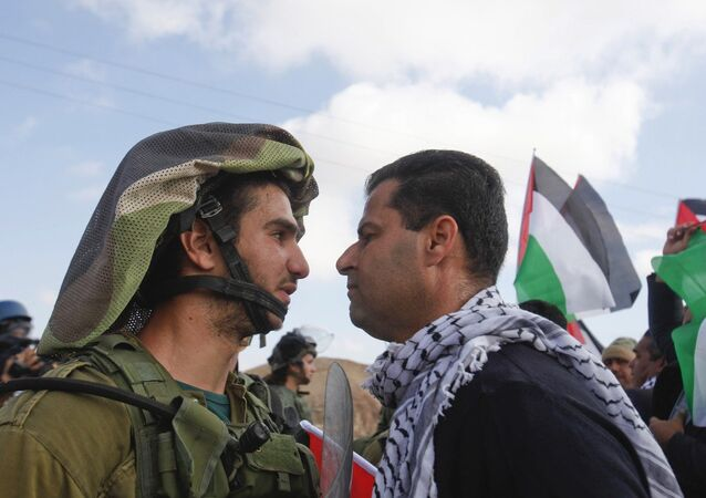 An Israeli soldier argues with a Palestinian protester