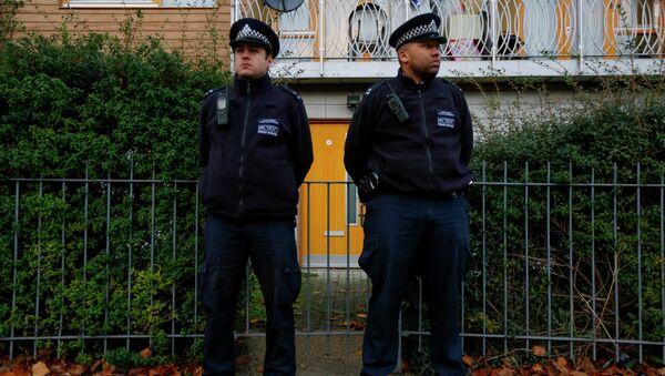 Police stand guard outside a South London - Sputnik International