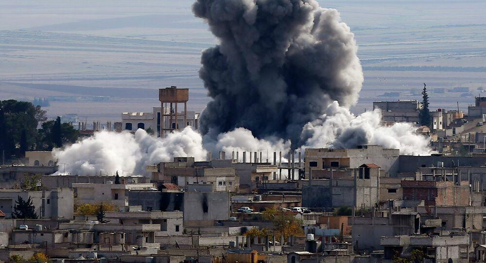 An explosion following an air strike is seen in western Kobani neighbourhood, November 23, 2014