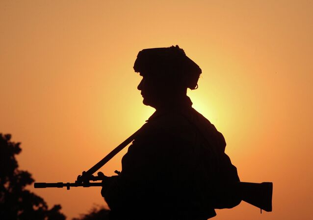 An Indian army soldier keeps vigil near the site of a gunbattle with suspected militants at Pindi Khattar village in Arnia near the border with Pakistan November 27, 2014