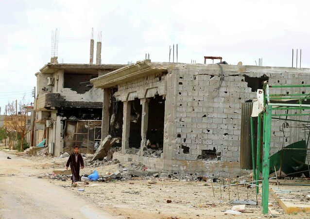 A boy walks next to the ruins of buildings in Benina, about 20 km east of Benghazi, November 21, 2014