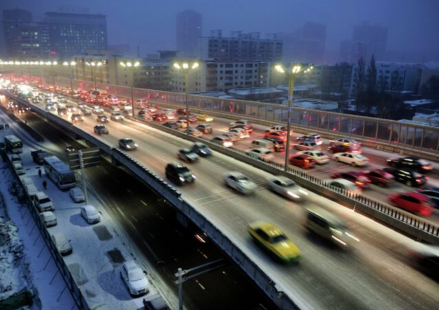 Cars drive along a bridge after snowfall in Urumqi, Xinjiang Autonomous region, November 28, 2014