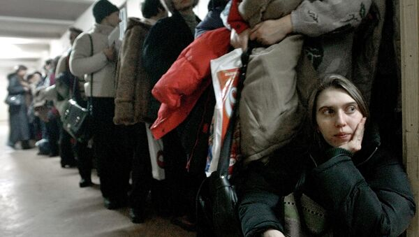 In this image dated Jan.28, 2004, showing a Romanian woman as she leans against the door at the International Office for Migration in Bucharest, Romania, Jan. 28, 2004, waiting in a line to apply for a job in Spain - Sputnik International