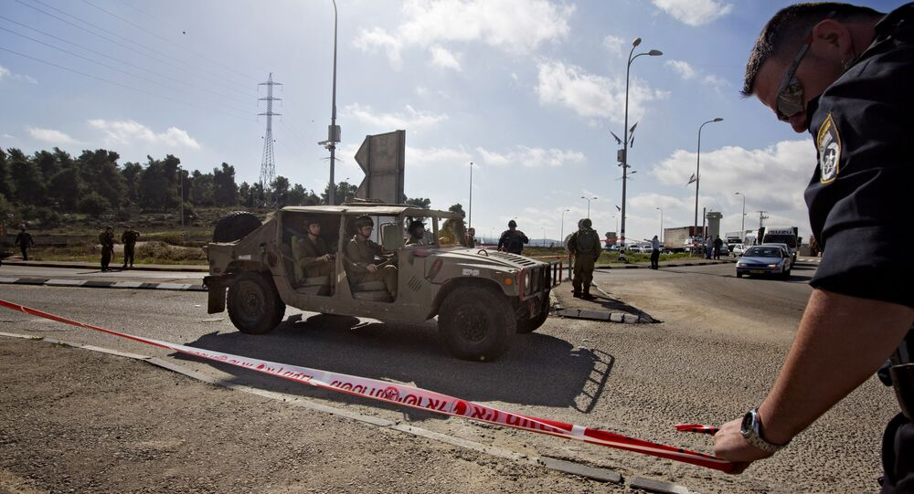Israeli soldiers and police officers stand at the scene of a stabbing attack at the West Bank Gush Etzion junction near Jerusalem