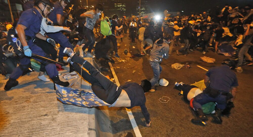 Police officers throw a pro-democracy protester on the main road outside government headquarters in Hong Kong