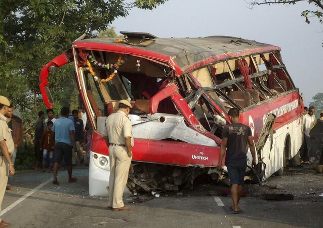 Police and Indian villagers look at the mangled remains of a passenger bus