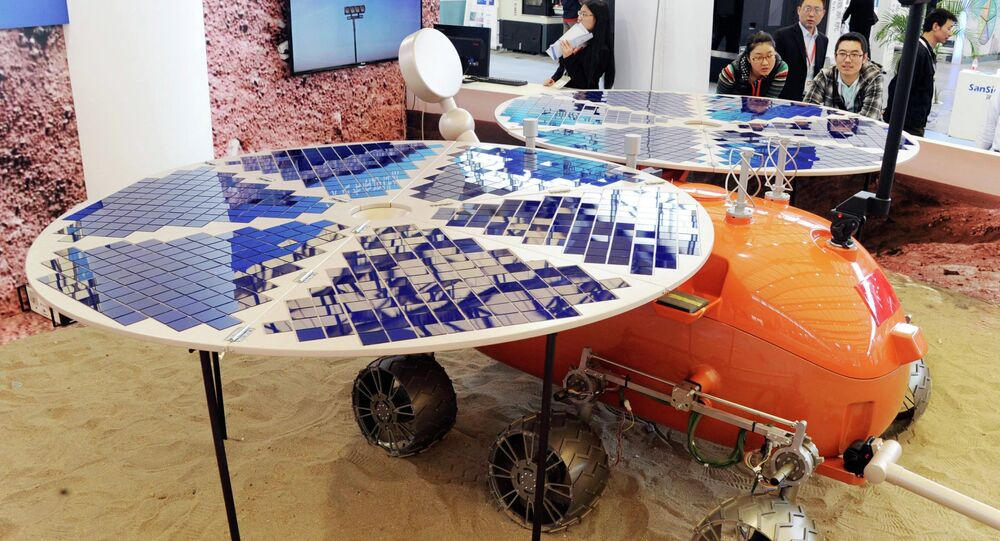 Visitors look at a prototype model of a Mars rover, which was designed and built in China, on display at the China International Industry Fair in Shanghai