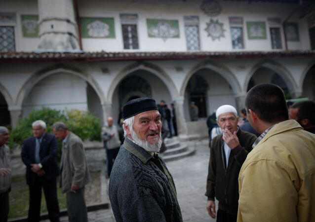 Crimean Tatars speak to each other after the prayer in a mosque marking the Eid al-Adha, celebrated by Muslims worldwide, in Bakhchisarai, Crimea