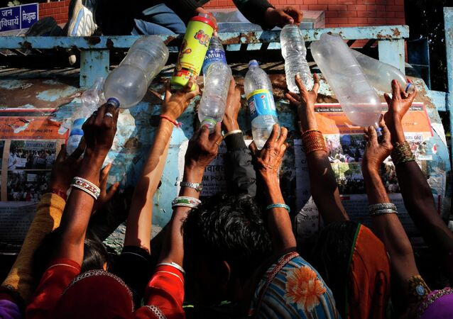 Indian women protesters from the Indian state fill their bottles with drinking water as they participate in a rally in New Delhi, India, Tuesday, Dec. 2, 2014