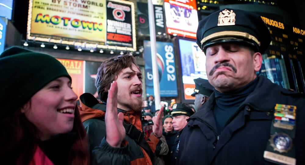 A NYPD policeman (R) reacts next to people protesting against the Staten Island death of Eric Garner during an arrest in July, at midtown Manhattan in New York December 3, 2014
