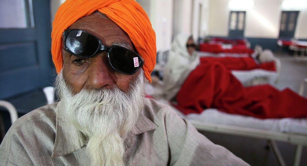 A man sits on a bed while waiting for treatment at a hospital after undergoing cataract removals from a free eye surgery camp, in the northern Indian city of Amritsar December 5, 2014