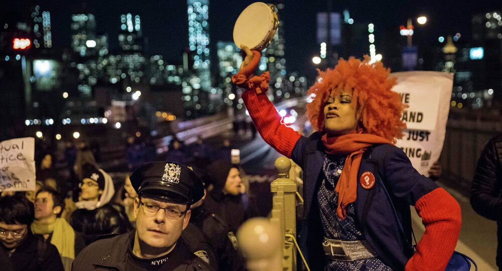 A female protester, demanding justice for Eric Garner, plays the tambourine
