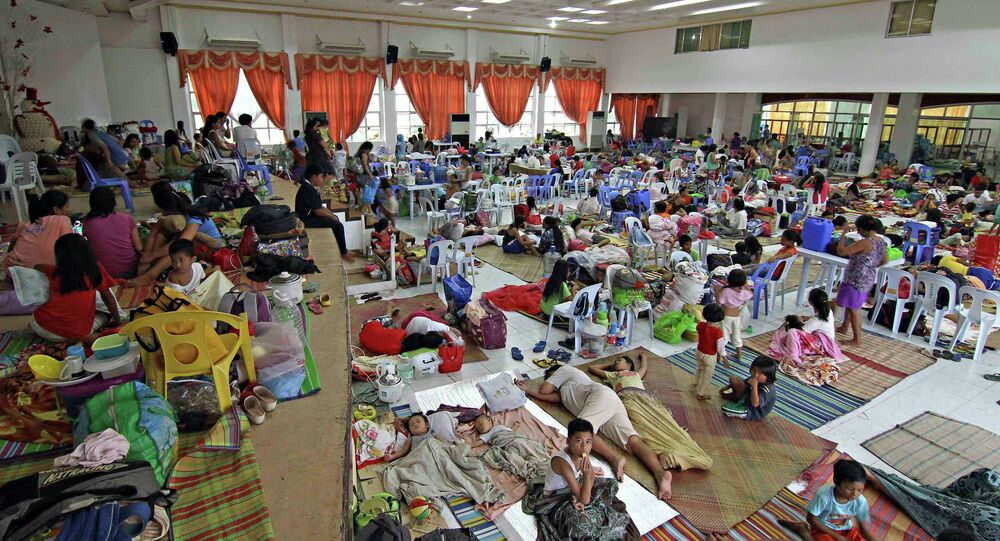 People take shelter inside a evacuation centre after evacuating from their homes due to super-typhoon Hagupit in Surigao city, southern Philippines December 5, 2014
