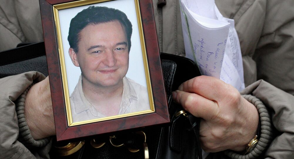 Portrait of lawyer Sergei Magnitsky who died in jail, is held by his mother Nataliya Magnitskaya, as she speaks during an interview with the AP in Moscow