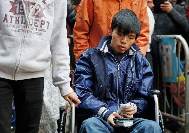 Student leader Joshua Wong attends a news conference as he sits on a wheel chair