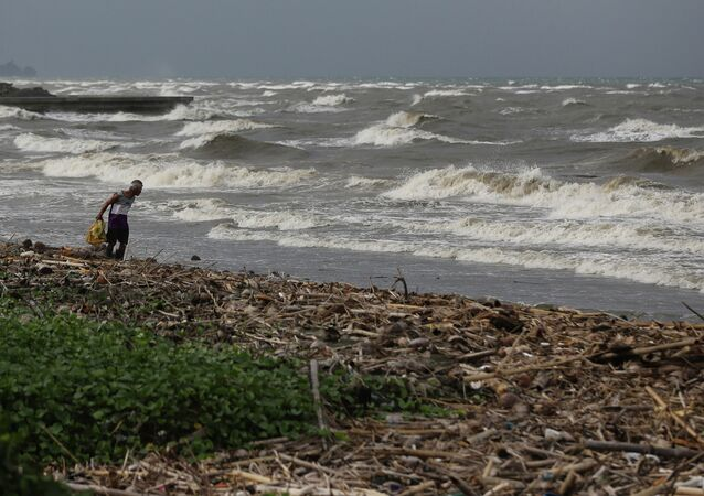 A man walks along the shore as strong waves from Typhoon Hagupit hit Atimonan, Quezon province, eastern Philippines on Saturday, Dec. 6, 2014