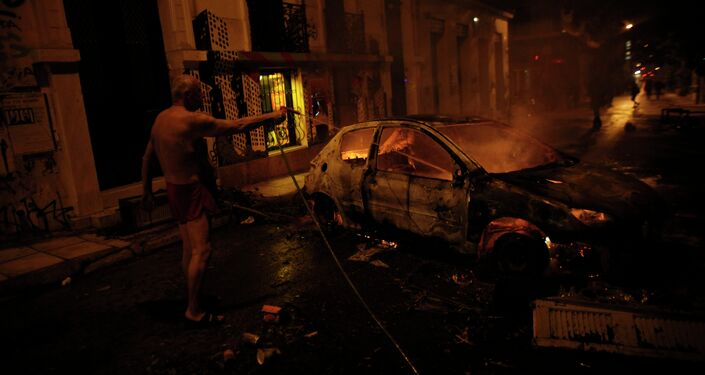 A local resident in his underwear tries to extinguish a burning car used by protesters as a barricade, during riots in Athens neighborhood of Exarchia