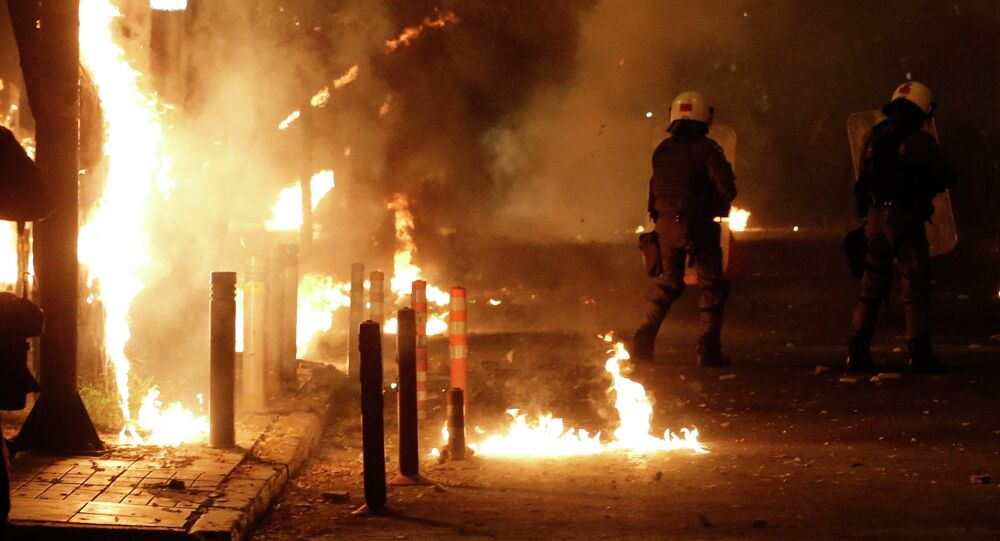 Riot police try to avoid petrol bombs thrown by protesters during clashes in the Athens neighborhood of Exarchia, a haven for extreme leftists and anarchists, on Saturday, Dec. 6, 2014