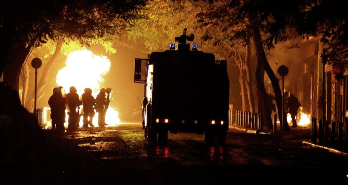 A police water cannon operates as riot police try to avoid petrol bombs during a protest in the Athens neighborhood of Exarchia, with a reputation of being a haven for extreme leftists and anarchists, on Saturday, Dec. 6, 2014