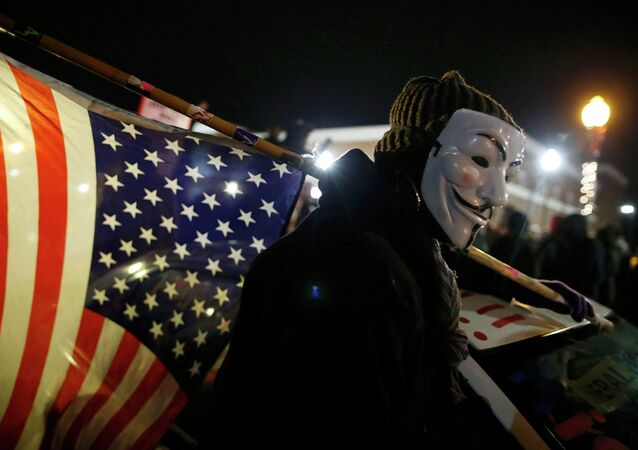 A protester wearing a Guy Fawkes mask carries an American flag outside the Ferguson Police Department in Ferguson, Missouri, November 24, 2014