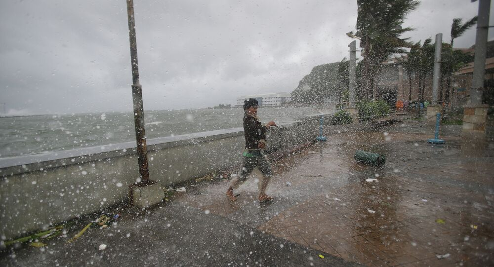 A man reacts as he strong winds and rain from Typhoon Hagupit hit shore in Legazpi, Albay province, eastern Philippines on Sunday, Dec. 7, 2014