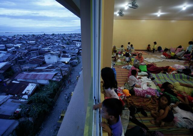 Children look out of a window at an evacuation centre for the coastal community, to shelter from typhoon Hagupit, near Manila, December 8, 2014