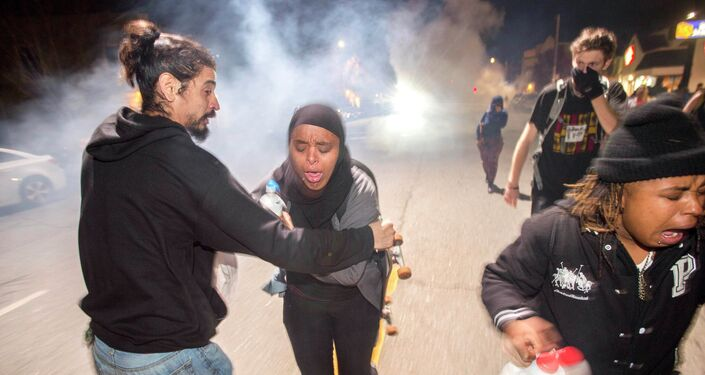 Protesters retreat while police officers deploy teargas to disperse a crowd comprised largely of student protesters during a protest against police violence in the U.S., in Berkeley, California December 7, 2014