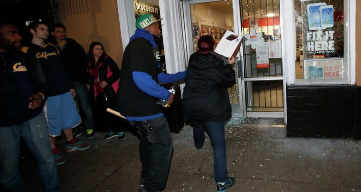 A woman attempts to toss back merchandise into a Radio Shack after it was vandalized during a march against the New York City grand jury decision to not indict a police officer in the death of Eric Garner, in Berkeley, California December 7, 2014