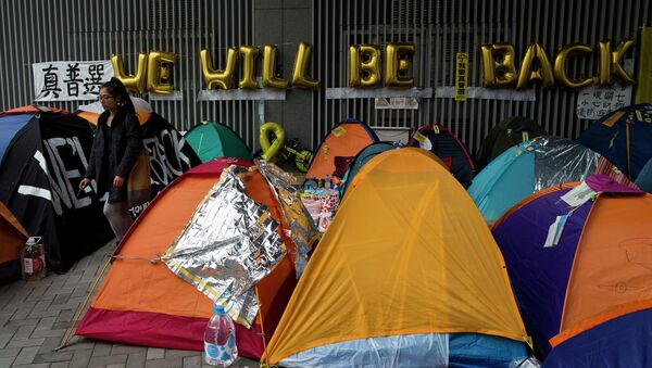 A pro-democracy protester walks past tents outside the government headquarters at Admiralty in Hong Kong December 10, 2014. - Sputnik International
