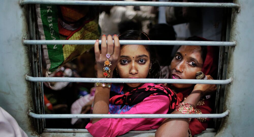 Murshida, 12, sits on the lap of her mother Marjina as the train leaves for their village in West Bengal, at a railway station in New Delhi, India