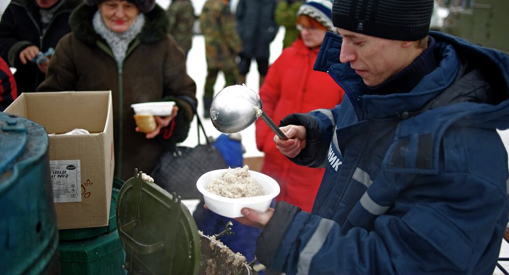 An emergency service worker distributes food just outside Luhansk, eastern Ukraine, Friday, Dec. 5, 2014, that has been without electricity and water since July