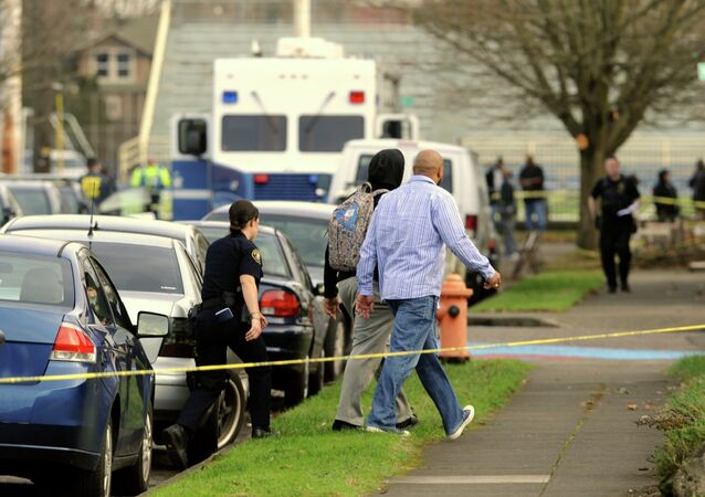 A student is evacuated by police from Rosemary Anderson High School in Portland