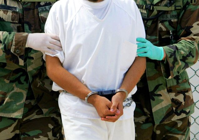 A detainee is escorted by military police at Camp 4 of the maximum security prison Camp Delta at Guantanamo Bay Naval Base
