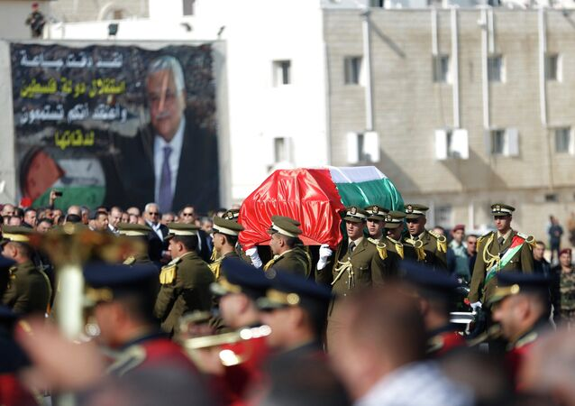 Palestinian honor guards carry a coffin containing the body of Palestinian minister Ziad Abu Ein during his funeral in the West Bank city of Ramallah December 11, 2014