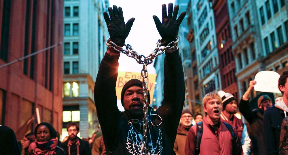 A man with a chain on his body takes part in a march against police violence, in New York December 13, 2014