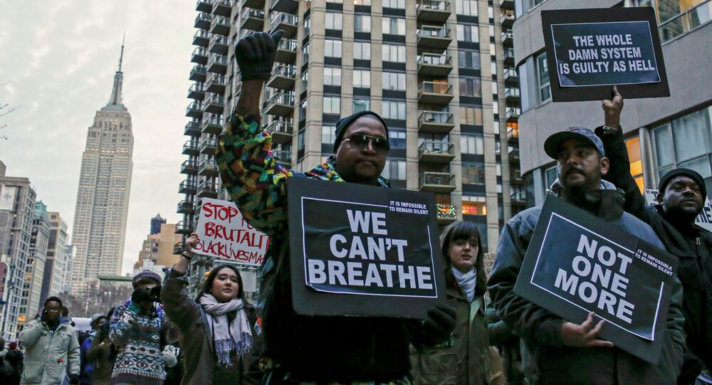 The Empire State Building is seen in the background while people march against police violence, in Midtown Manhattan, New York December 13, 2014