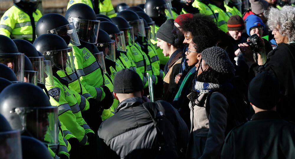 Demonstrators face a line of police officers during a demonstration against recent grand jury decisions not to indict police officers in the deaths of Michael Brown and Eric Garner, in Boston, Massachusetts December 13, 2014